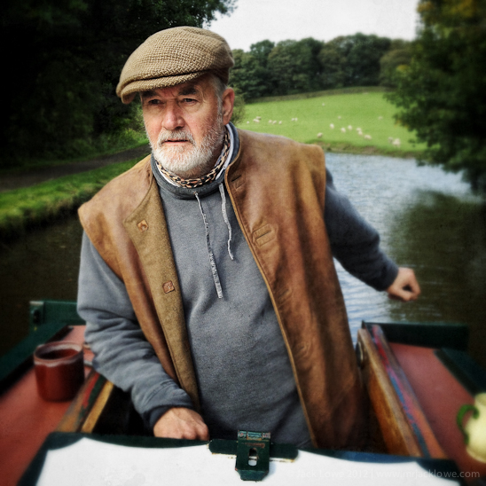Captain Duncan Davis at the tiller of his heritage narrowboat, Pearl Barley