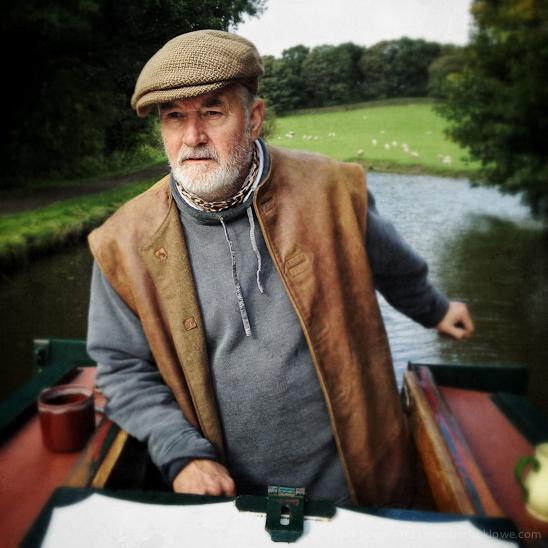 Captain Duncan Davis at the tiller of his heritage narrowboat, Pearl Barley